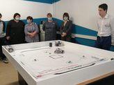 на картинке группа людей наблюдают за роботом